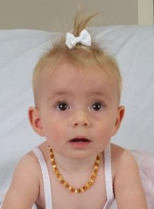 baby with polished amber teething necklace